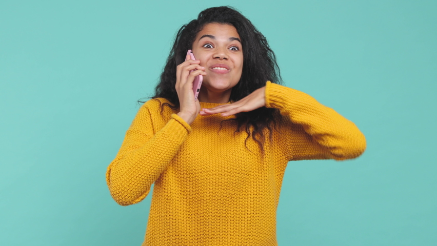 Excited happy young african american woman 20s years old in yellow sweater posing isolated on blue turquoise background studio. People lifestyle concept. Talk on mobile cell phone doing winner gesture | Shutterstock HD Video #1063109308