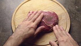 Timelapse video of cooking beef steak at home.Flat lay footage filmed directly from above on kitchen table.Fresh raw piece of tenderloin beefsteak being prepared for grilling for dinner