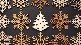 Flat lay video clip of wooden snowflakes and Christmas tree for home decor.Decorate house with hand made toys made from natural wood material,filmed from above in 4K ultra hd video clip