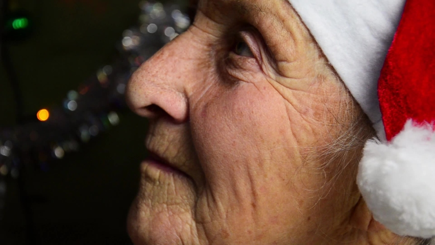 Grandmother in Santa hat for New Year. Happy grandmother in a New Year's hat. An old grandmother waiting for the new year. Close-up of wrinkled face of old grandmother. Old woman on New Year's Eve Royalty-Free Stock Footage #1063124188