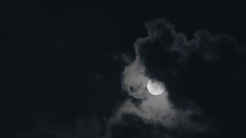 Full moon on dark cloudy night. Clouds passing by the moon in spooky feeling like thriller and horror films. Werewolf moon, dark night sky, black clouds, full moon clouds, ghost, horror films.  | Shutterstock HD Video #1063124623