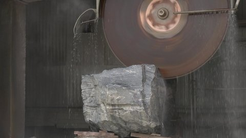 Stone-processing industry theme with rock and circular saw. Granite sawing machine in a factory from a quarry.  marble cutting factory, marble cooled with water while being cut - industrial