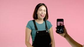 Smiling vlogger woman recording video of herself dancing in front of smartphone camera on pink background. Influencer makes funny social media clip