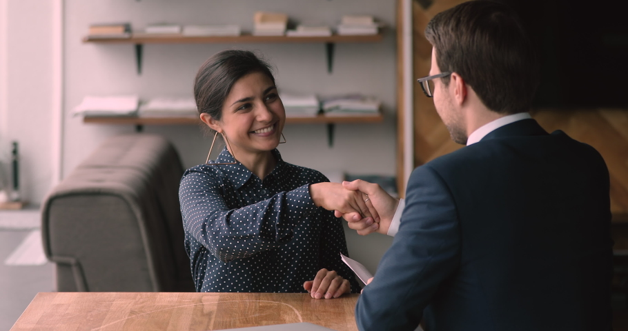 Indian ethnicity 25s confident female applicant passing job interview finish formal appointment shaking hands with male employer. Successful business meeting, making deal, hr, company staffing concept Royalty-Free Stock Footage #1063137853