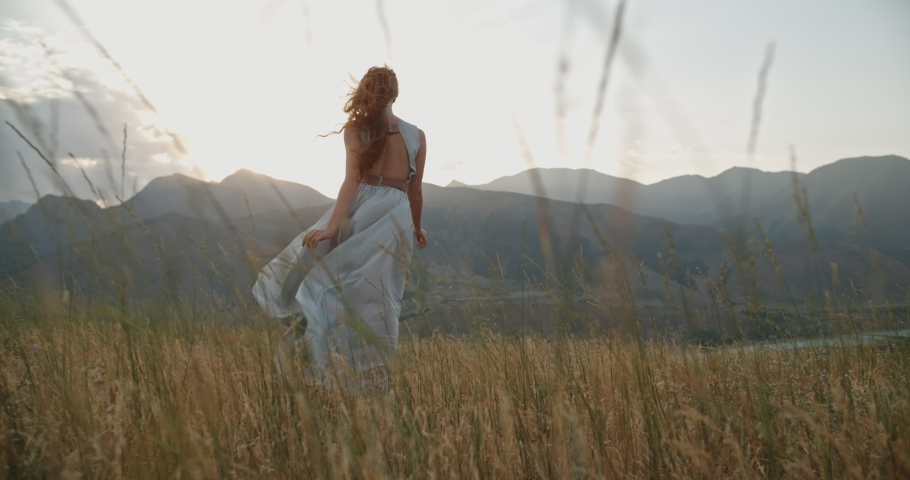 Young beautiful girl with red hair wearing white dress running on top of a mountain facing wind blowing her hair and dress and smiling - freedom, adventure, harmony 4k footage Royalty-Free Stock Footage #1063141084