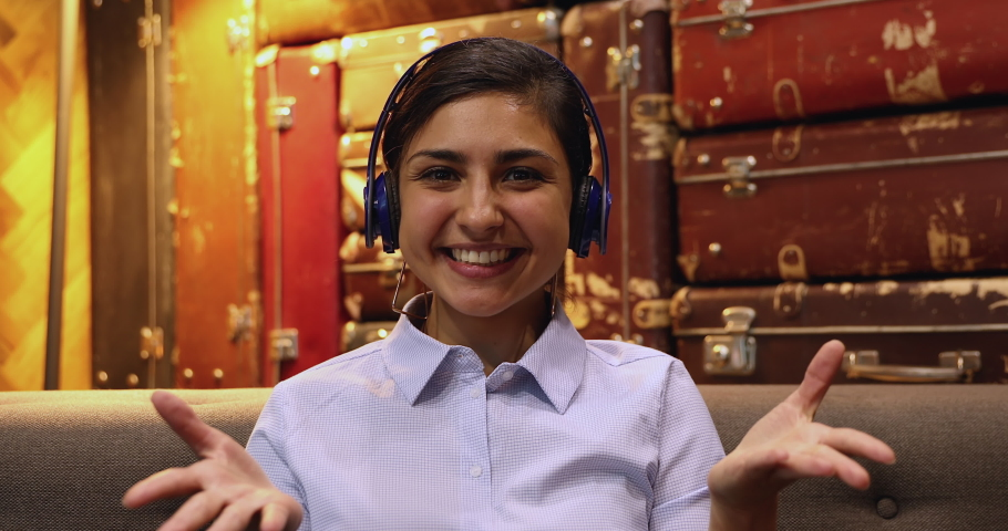Head shot portrait 30s pleased Indian businesswoman sitting in cozy lounge office room wear headphones conduct business meeting negotiations use video call, webcam view. Remote communications concept