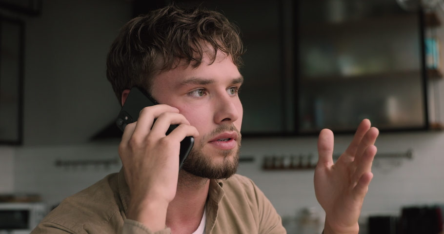 Close up view millennial man sitting in kitchen holding wireless device talking to client having serious conversation on mobile phone, working making business remotely use modern technologies concept