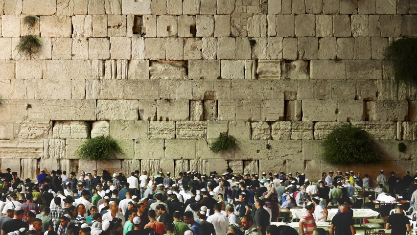 Religious ritual at holiest site israel. Jew pray for Yom Kippur and Rosh Hashanah blessing holidays. Crowd of Jewish people praying at the holy western wall big rock in the old city of Jerusalem