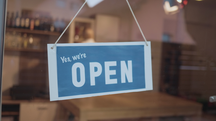 Woman in apron closing the bar due to covid-19 problems. Middle shot od open-close sign on the door of a bar. | Shutterstock HD Video #1063158553