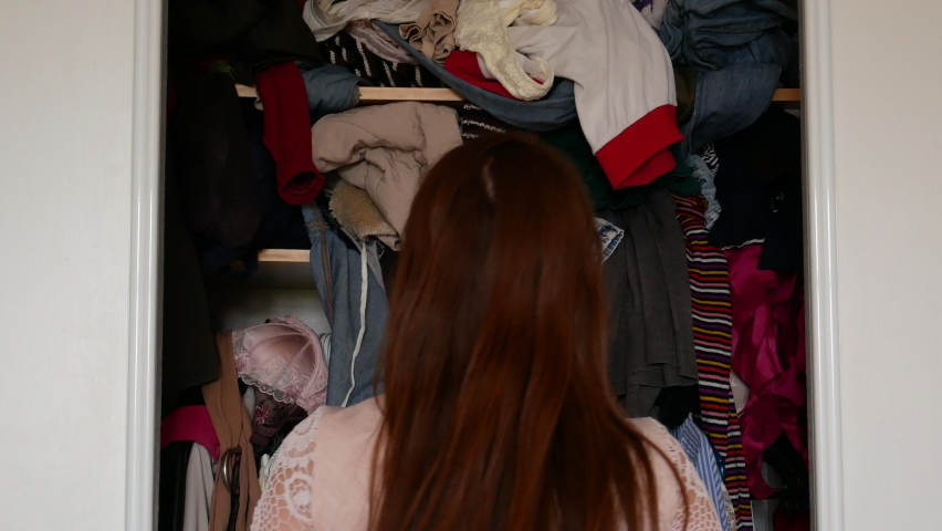 The girl is trying to get the dress out of the closet. All the clothes fall on top of her. Wardrobe mess, 4k video. Royalty-Free Stock Footage #1063158907