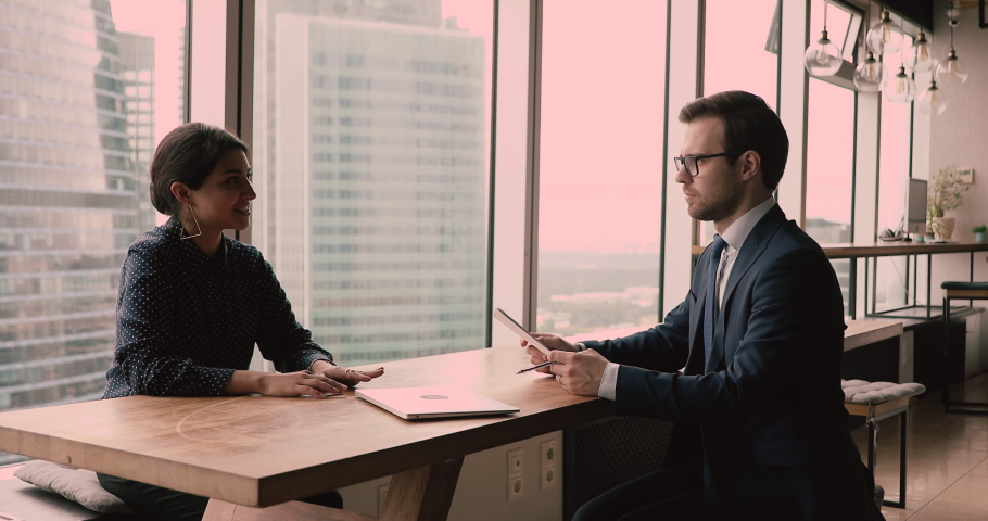 Talk during formal meeting, business negotiations concept. Indian and Caucasian businesspeople communicating during meeting in modern skyscraper office. Vacancy candidate pass job interview concept Royalty-Free Stock Footage #1063167001