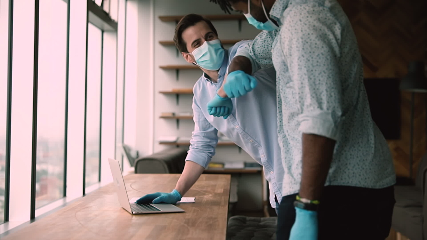 Multiracial friendly employees in face masks and protective gloves during meeting in office greeting each other making elbow bump, to avoid contagious disease covid-19 spread. Personal safety concept Royalty-Free Stock Footage #1063167070