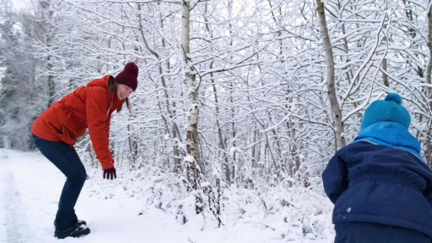 Family winter fun activity. Slow motion caucasian mother and little child boy plays snowballs in snowy park. Royalty-Free Stock Footage #1063172494