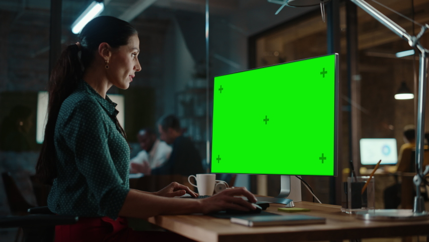 Middle Aged Multiethnic Specialist Working on Desktop Computer with Green Screen Mock Up Display in Busy Creative Office. Beautiful Diverse Female Manager in Green Polka Dot Blouse. Royalty-Free Stock Footage #1063172731