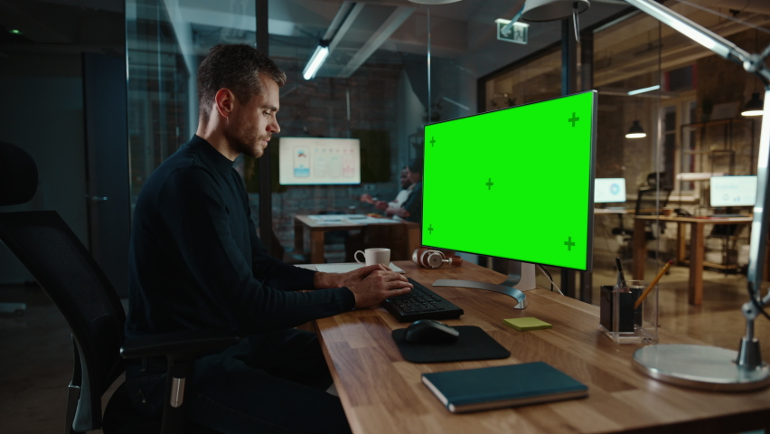 Young Handsome Specialist Working on Desktop Computer with Green Screen Mock Up Display in a Busy Creative Office with Colleagues. Male Manager with Trimmed Beard is Wearing a Casual Black Jumper. Royalty-Free Stock Footage #1063173079