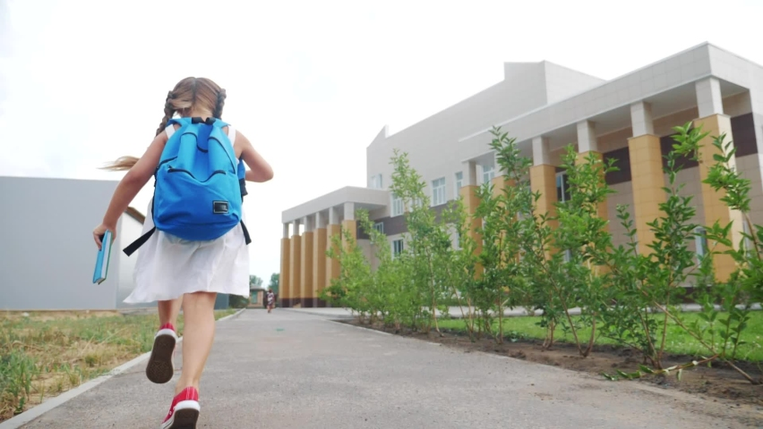 Little girl kid with a backpack and a textbook runs hurrying to school. education concept. little schoolgirl with a backpack fun runs to the school building. child running with textbook back view | Shutterstock HD Video #1063173676