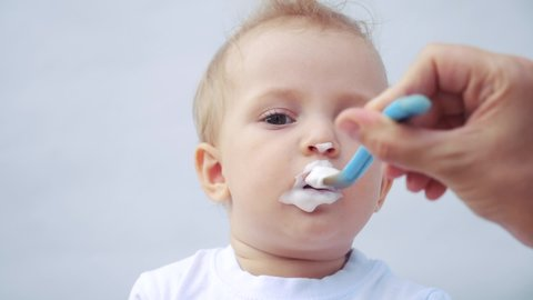 newborn baby eats from a spoon, close-up portrait grimy face. newborn baby at home kid dream concept. Newborn baby son gets dirty and eats with pleasure. baby and mom at fun home