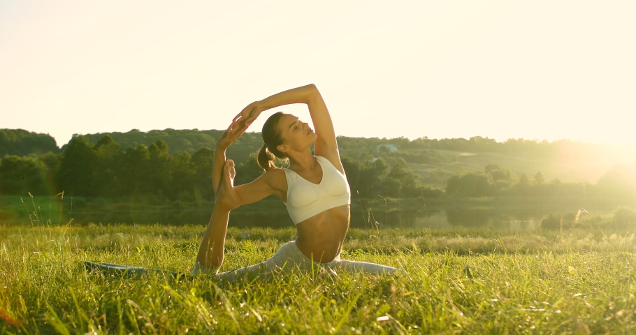 Caucasian beautiful slim young woman sitting on green grass on sunny day and stretching leg and side back in sunlight. Pretty sporty female yogi in asana early in the morning. Physical training.