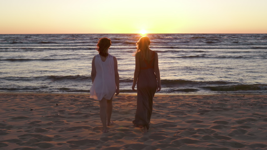 Two young lesbian women walk together towards sunset
