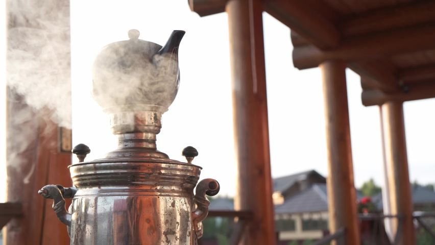 Boiling russian samovar with steam and brewing teapot on the top. Tea party on terrace of country house. Royalty-Free Stock Footage #1063193533