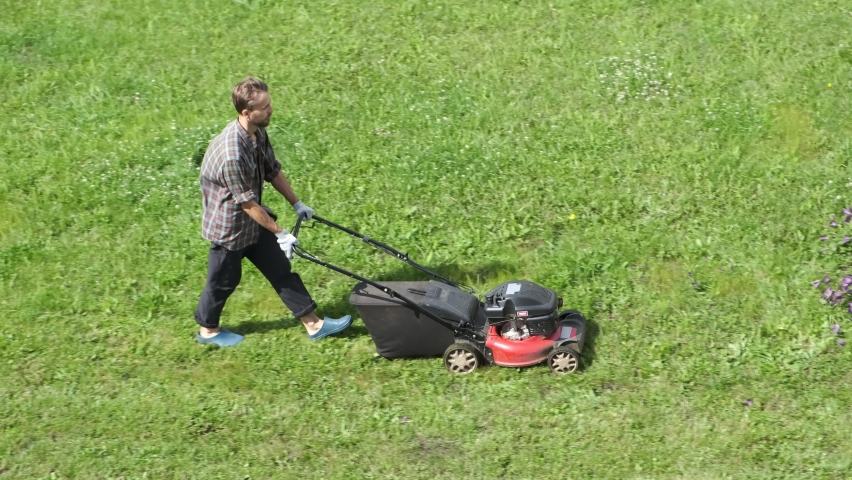 Top view of male worker mowing green grass lawn with motorized lawnmower. Landscaping service, gardening maintenance. Royalty-Free Stock Footage #1063193557