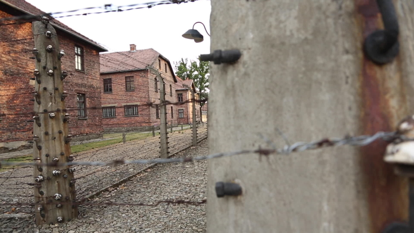 Auschwitz Poland Tracking Slowly By Barbed Wire Fence With Buildings Behind