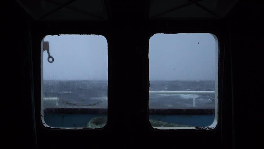 Storm view from cabin window. Strong side pitching. Sea view from ship windows. Waves crash against side and spray covers sky. Very strong storm. High waves with foam are visible through portholes. | Shutterstock HD Video #1063208446