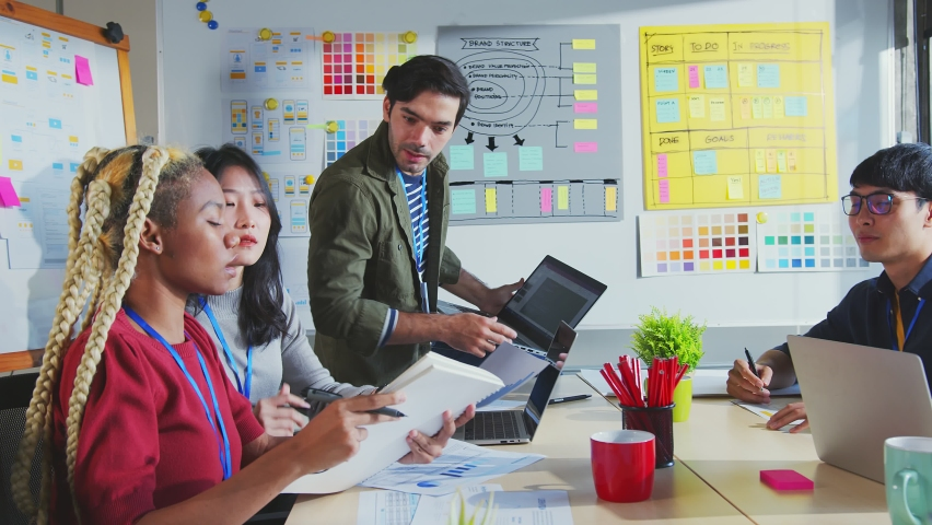 Meeting of UX developer and UI designer brainstorming about mobile app interface workflow design on table with coworker breif and color code at co-working space.Creative digital development agency. Royalty-Free Stock Footage #1063214212