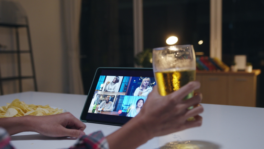 Young Asia lady drinking beer having fun happy moment night party event online celebration via video call in living room at home at night. Social distancing, quarantine for coronavirus prevention. Royalty-Free Stock Footage #1063219060