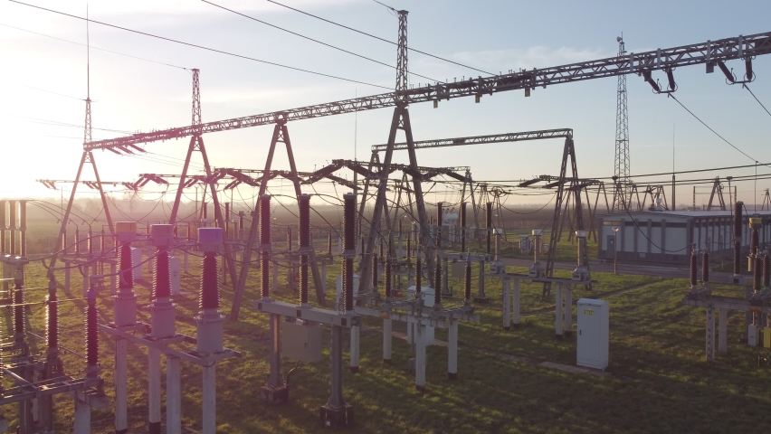 Transformer : The equipment used to raise or lower voltage, high voltage power station. Top view from flying drone. Wide angle, high voltage substation with tall pylons and voltage distribution cables | Shutterstock HD Video #1063225165