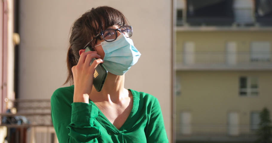 Close up of a brunette woman, wearing glasses, makes a phone call with a mask during lockdown