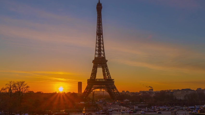 4K timelapse of Paris at sunrise with the Eiffel Tower at the Trocadero gardens and the traffic,the most famous landmark in Paris,France.Golden hour in an autumn winter sunny day