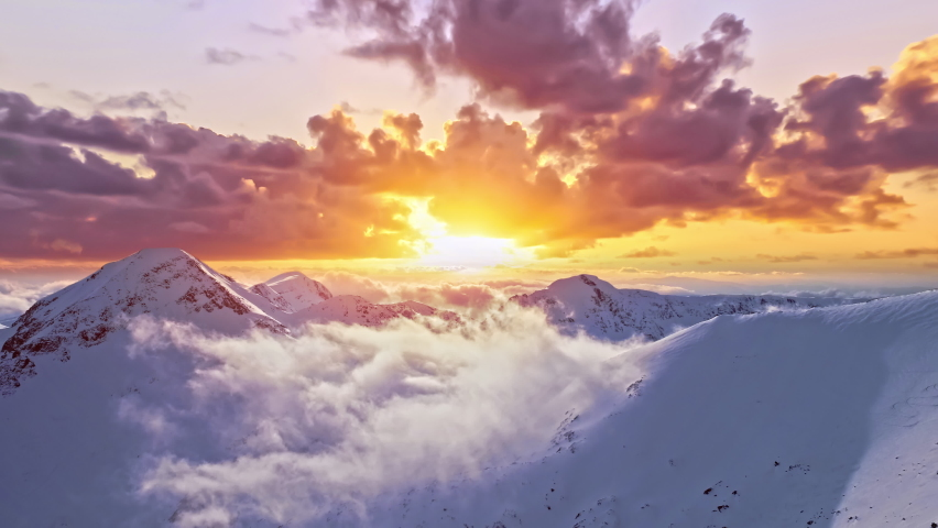 Flying Through Clouds Above Mountain Tops Paradise Heaven Eternity Creation Mountain Range Winter Snow Cold Sunset Sunrise Golden Hour High Peaks Wonderful Inspiring Natural Landscape 4K Royalty-Free Stock Footage #1063234465