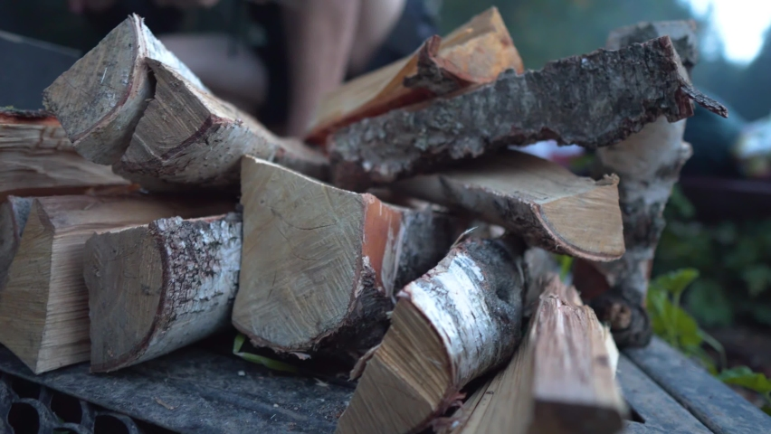 Smooth movement: Birch Firewood for a Campfire in the Evening in nature. In the background, the foot of a person is moving, lighting a fire. Royalty-Free Stock Footage #1063235935