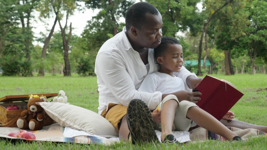 Low angle shot of a happy African family outing at park concept. Outdoors, medium shot of dark skin, kind father and a son picnic at the park, sitting on the mat, and reading a book together.