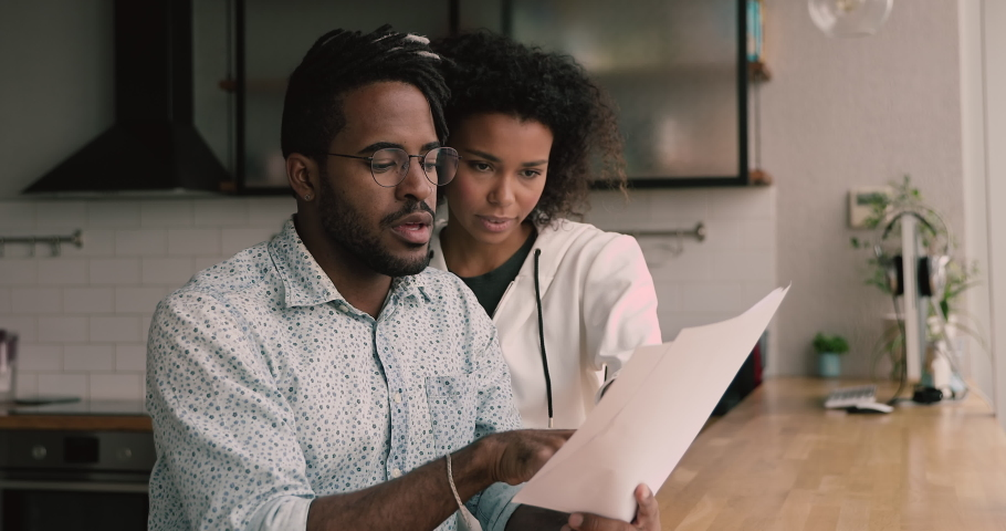 African married young couple holding papers read received correspondence letter document sit at apartment in kitchen, manage family finances, discuss money spend, expenses, get info about taxes refund Royalty-Free Stock Footage #1063237930
