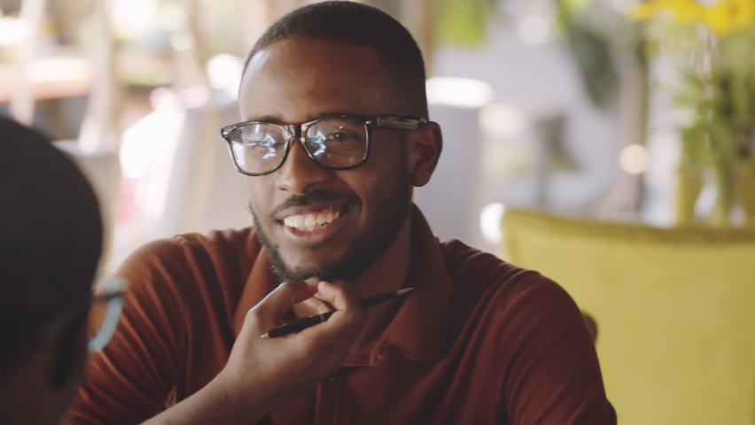 Over the shoulder shot of young cheerful afro-american man greeting colleague with fist bump, sitting at cafe table and discussing business on lunch