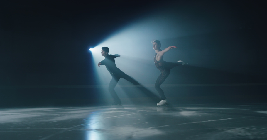 Cinematic shot of young couple of artistic figure skaters is performing a pair skating choreography on ice rink before start of a competition. Concept of perfection, precision, freedom, passion. | Shutterstock HD Video #1063242904