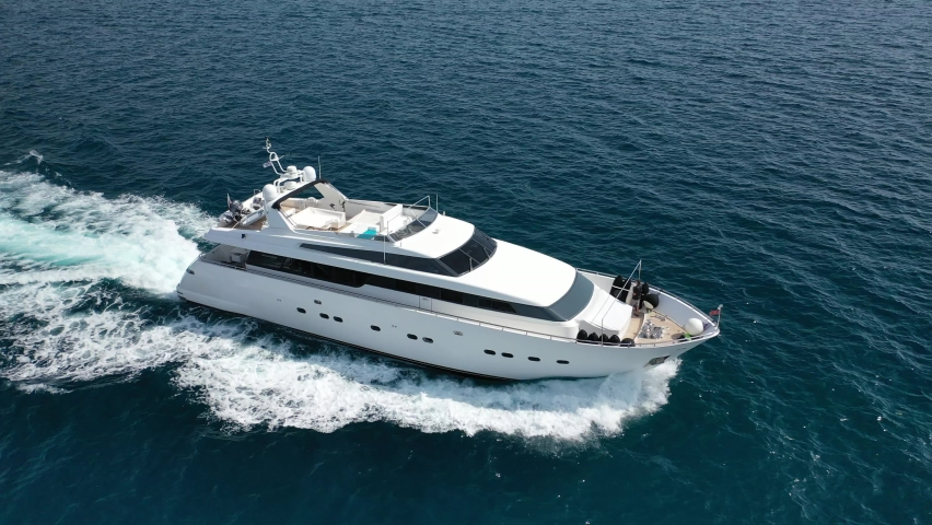 Aerial drone tracking video of luxury yacht cruising in deep blue open ocean sea