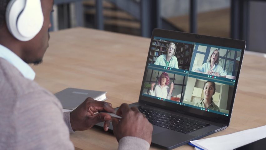 African business man having virtual team meeting on video conference call using laptop working from home office talking to diverse colleagues in remote videoconference online chat. Over shoulder view Royalty-Free Stock Footage #1063245025