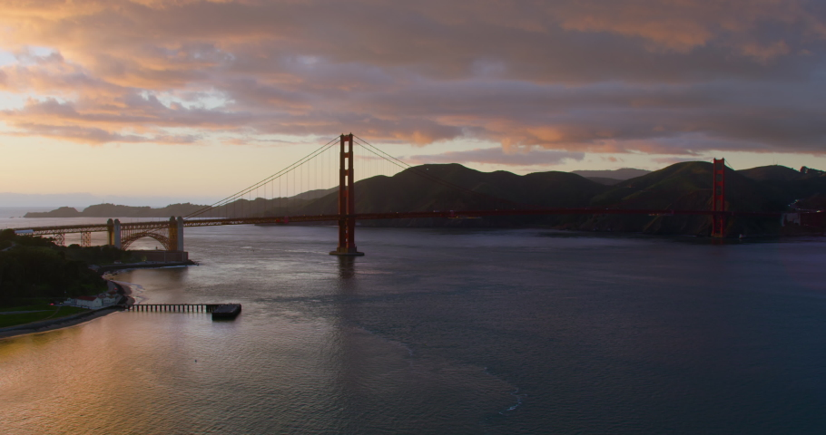Aerial view of the magnificent Golden Gate Bridge during sunset. This bridge connects the San Francisco peninsula to Marin County. US route 101 and SR 1 full of cars. Shot on Red 8K.