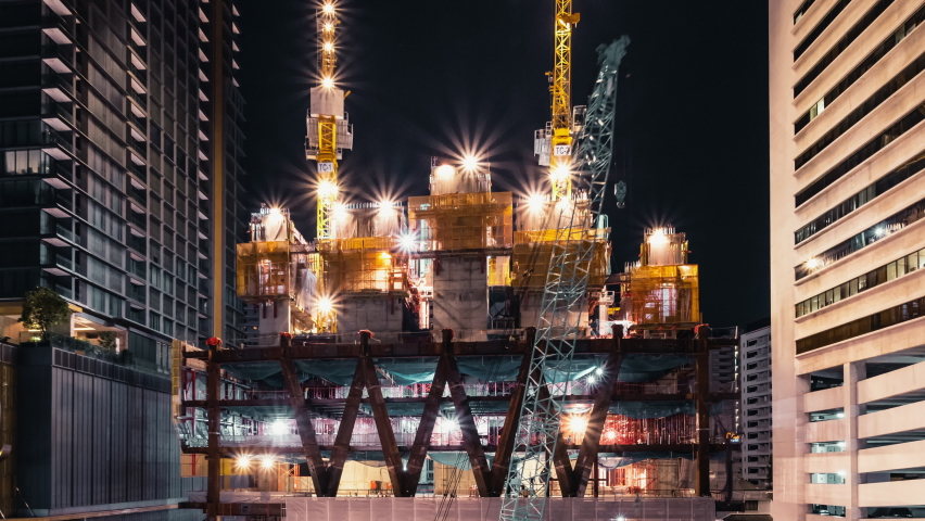 Time-lapse of crane and construction worker in under construction building site at night. Construction industry, industrial business, or civil engineering technology concept. Tilt down Royalty-Free Stock Footage #1063260376