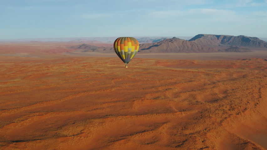 Breathtaking scenic aerial view of a hot air balloon flying over the endless sand dunes of the Namib desert, Namibia