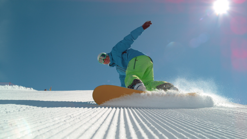 SLOW MOTION TIME WARP, LOW ANGLE, CLOSE UP, DOF: Athletic male tourist shredding the slopes sprays snow at the camera. Snowboarder carves along a groomed ski slope of a ski resort in the sunny Alps.