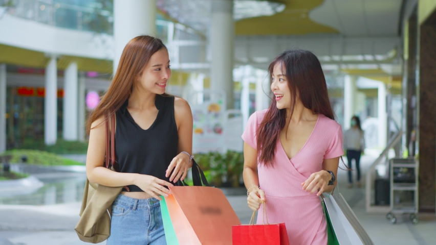Two happy Asian young women shopping outdoor in department store during sale season at end of the year. The girls holding shopping bag walking with happiness and smile enjoy purchasing things together Royalty-Free Stock Footage #1063271857