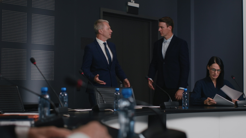 Expert group taking seats and working together at official event. Political speaker talks at meeting room of modern business forum. Man in suit discusses partnership at conference in convention hall Royalty-Free Stock Footage #1063272460