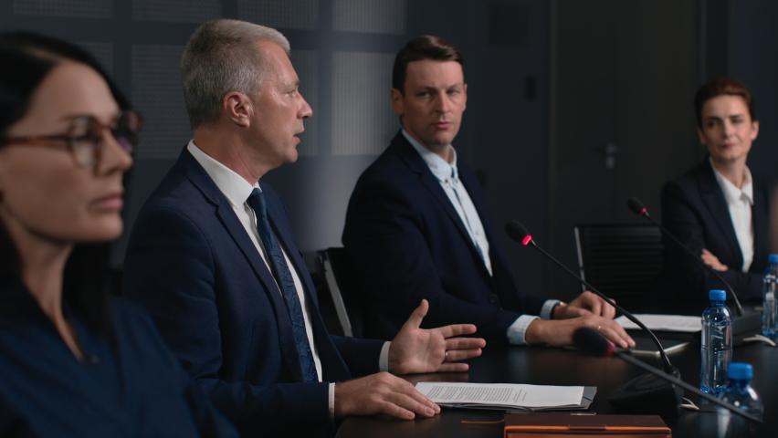 Political speaker talks at meeting room of business forum. Man in suit discusses partnership at conference in convention hall. Expert group works together on important information at official event Royalty-Free Stock Footage #1063272472