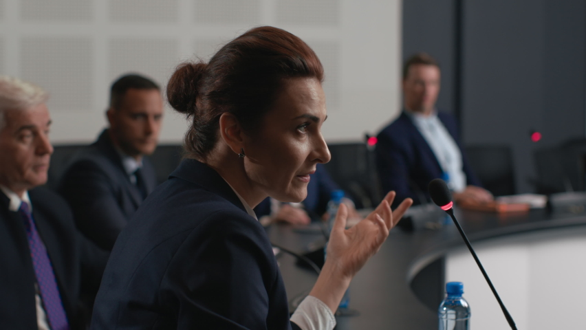 Political speaker talks at meeting room of modern business forum. Adult woman in suit discusses partnership at conference in convention hall. Expert group of colleagues works at official event closeup Royalty-Free Stock Footage #1063272478
