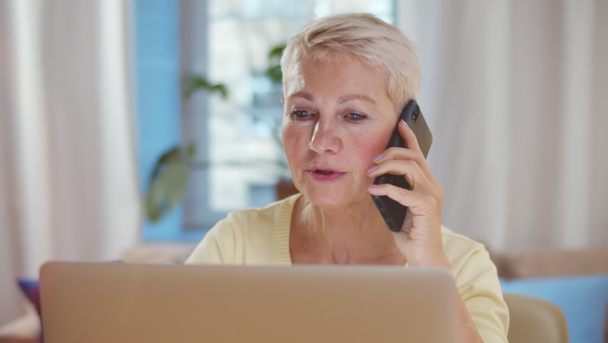 Elderly woman talking on cellphone while working on laptop at home. Portrait of senior businesswoman having phone call and working on computer remotely at home