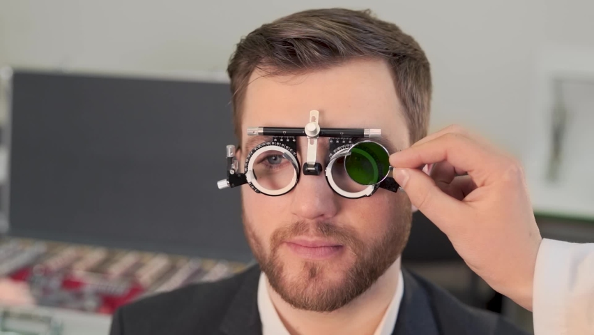 A large portrait of a pretty man picks up lenses for new glasses | Shutterstock HD Video #1063276840